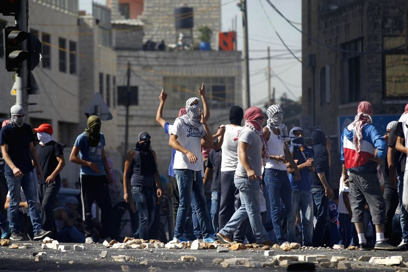 Palestinians are seen during clashes with Israeli policemen in Shuafat, an Arab neighborhood of northeastern Jerusalem, on July 2, 2014. Israeli security forces ...