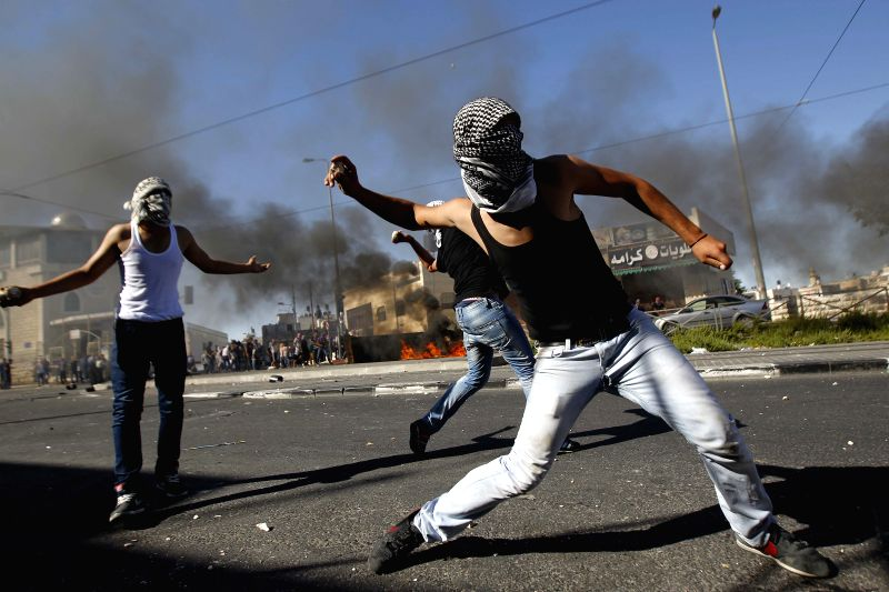 Palestinians hurl stones during clashes with Israeli policemen in Shuafat, an Arab neighborhood of northeastern Jerusalem, on July 2, 2014. Israeli security forces