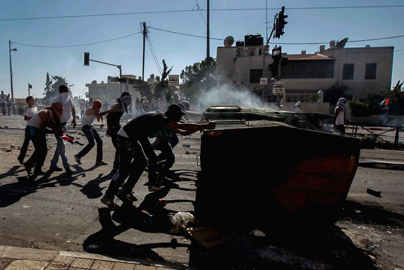 Palestinian shoot during clashes with Israeli policemen in Shuafat, Jerusalem, on July 3, 2014. Israel policemen faced a second day of violent Palestinian protests