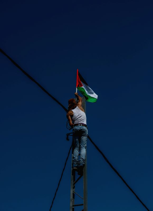 A Palestinian demonstrator climbs up to erect a Palestinian flag during clashes between Palestinian demonstrators and Israeli policemen in Shuafat, an Arab ...