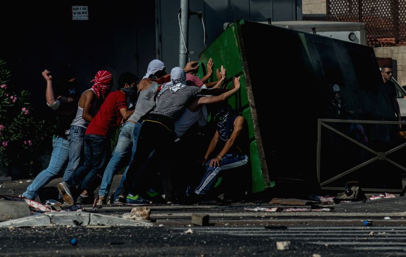 Palestinian demonstrators confront with Israeli policemen during clashes in Shuafat, an Arab neighborhood of northeastern Jerusalem, on July 4, 2014. Hundreds of ..