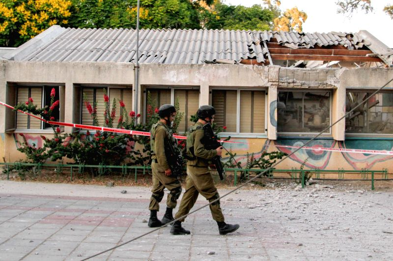 Israeli soldiers walk past a building hit by a rocket fired from the Gaza Strip near the border between southern Israel and Gaza, on July 9, 2014. Since Israel ...