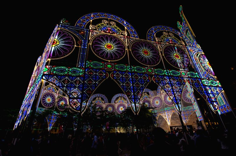 Visitors look at a piece of illumination work at Jaffa Gate in the Old City of Jerusalem, on June 19, 2014. The sixth Jerusalem Festival of Light is closed on ...