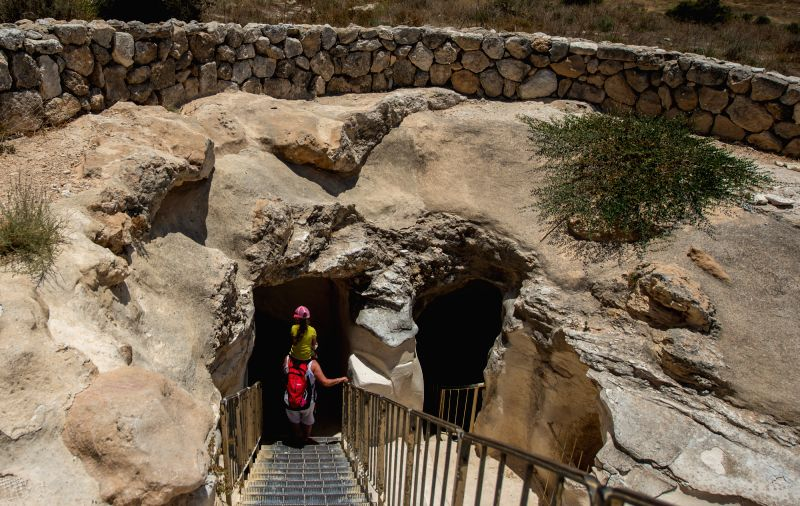A woman carrying her daughter enters an Oil Press Cave at Bet-Guvrin and Maresha National Park, Israel, on June 28, 2014. This is one of 22 underground oil ...