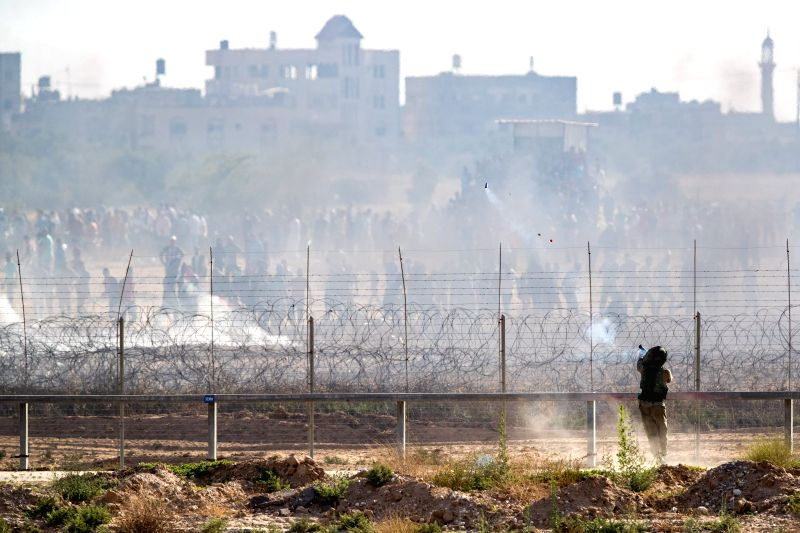 JERUSALEM, June 9, 2018 - Israeli security forces fire tear gas toward Palestinian protesters along the barrier between Gaza and Israel, on June 8, 2018.