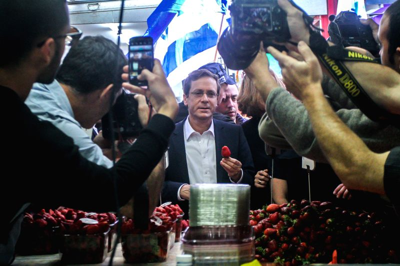Israel's Zionist Union leader Isaac Herzog (C) is seen during a campaign stop at a fruit and vegetable market in Tel Aviv, Israel, on March 12, 2015. Israeli ... - Benjamin Netanyahu