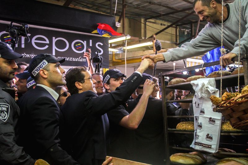 Israel's Zionist Union leader Isaac Herzog (3rd L, Front) shakes hands with a vendor during a campaign stop at a fruit and vegetable market in Tel Aviv, Israel, ... - Benjamin Netanyahu