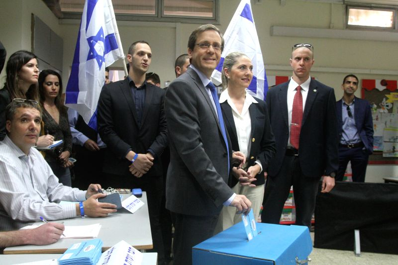 Israel's Zionist Union leader Isaac Herzog (C) casts his ballot at a polling station during the parliamentary election in Tel Aviv, Israel, on March 17, 2015. ...