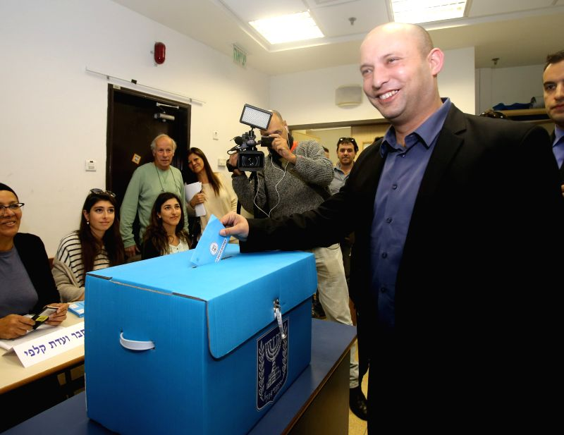Israeli Economy Minister and Jewish Home leader Naftali Bennet casts his ballot at a polling station during the parliamentary election in Raanana, Israel, on ...