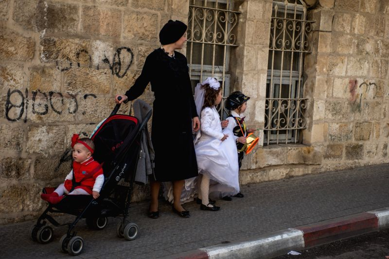A dressed-up Jewish family linger on during Purim holiday at Mea Shearim in Jerusalem, on March 6, 2015.Purim is one of the most joyous and fun holidays on the ...