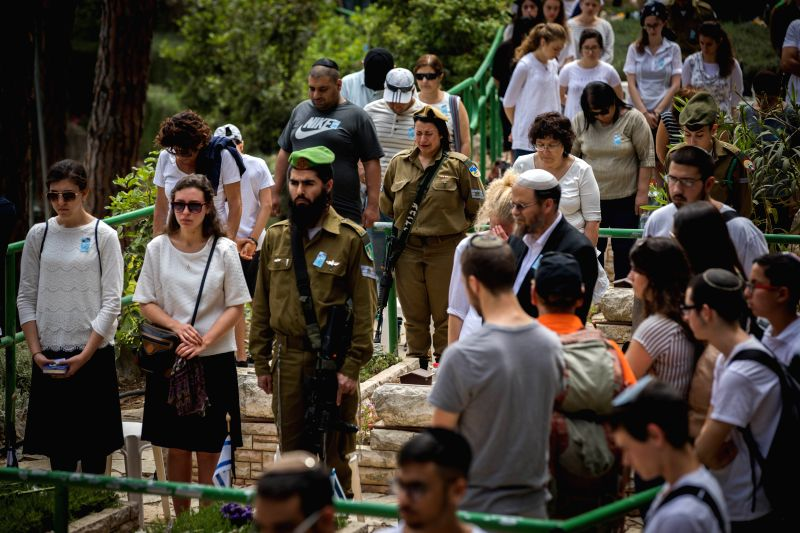 JERUSALEM, May 1, 2017 - Bereaved Israelis mourn next to graves of fallen soldiers at the Mt Herzl military cemetery in Jerusalem, on May 1, 2017. Israel came to a standstill on Sunday evening, ...