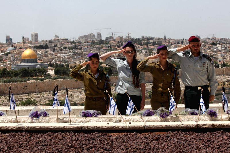 Israeli soldiers salute after placing Israeli national flags on the graves of fallen soldiers at the military cemetery on the Mount of Olives in the Old City of ...