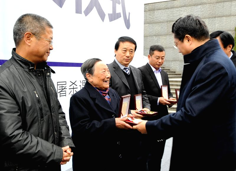 Xia Shuqin (2nd L), a survivor of the Nanjing Massacre, receives the special contribution award during an awarding ceremony at the Memorial Hall of the Victims in Nanjing Massacre by ...
