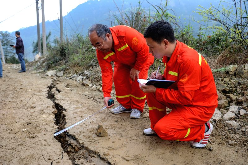 Seismology researchers check the damage of a road at Liuji Village in Jianhe County, southwest China's Guizhou Province, March 31, 2015. People in the region have ...