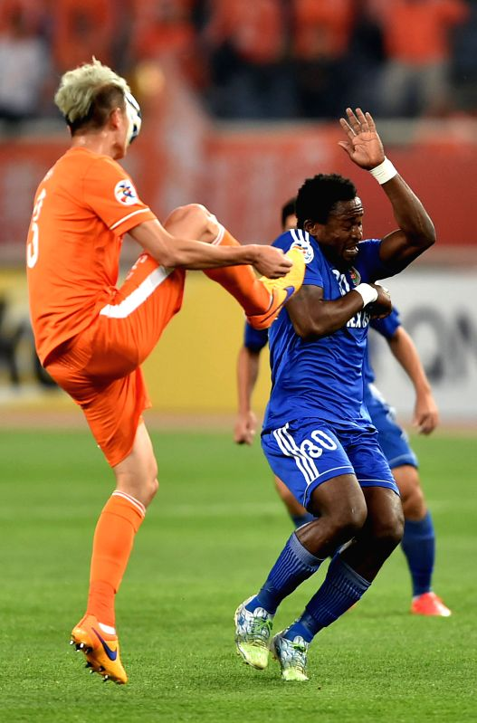 G.B Oseni (R) of Vietnam's Becamex Binh Duong vies the ball with Dai Lin of China's Shandong Luneng FC during a Group E match at the AFC Champions League 2015 in ...