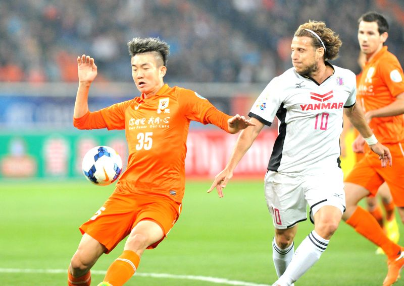 Dai Lin (L) of China's Shandong Luneng FC vies with Diego Forlan of Japan's Cerezo Osaka during their 2014 AFC Champions League Group E match in Jinan, capital of ...
