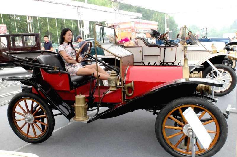 A model presents a Hupmobile antique car during an exhibiton of American classic antique cars in Jinan, capital of east China's Shandong Province, Aug. 30, 2014.  ...