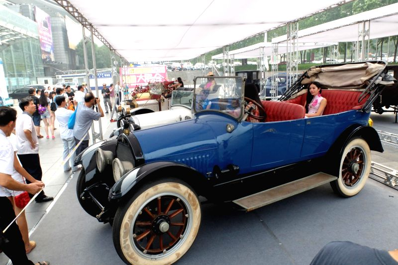 Visitors view antique cars during an exhibiton of American classic antique cars in Jinan, capital of east China's Shandong Province, Aug. 30, 2014.  (Xinhua/Xu ...