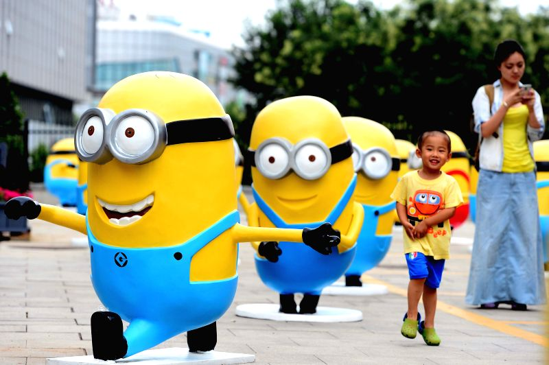 "A boy plays around among minions figures in Jinan, capital of east China's Shandong Province, July 12, 2014. Figures of minions from movie ""Despicable Me"" .."
