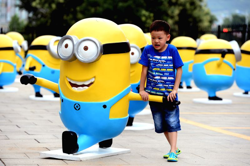 "A boy poses for photo with a minion figure in Jinan, capital of east China's Shandong Province, July 12, 2014. Figures of minions from movie ""Despicable Me"