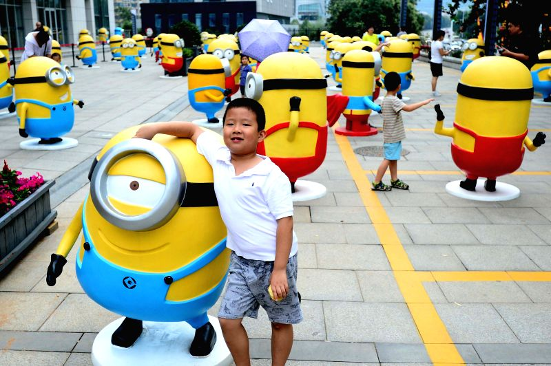"Citizens pose for photos with minions figures in Jinan, capital of east China's Shandong Province, July 12, 2014. Figures of minions from movie ""Despicable ..."