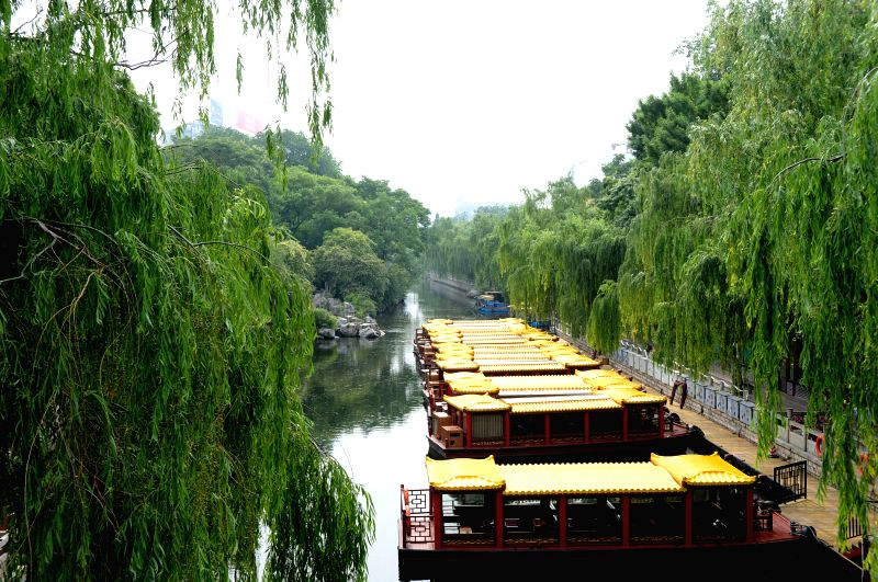 Painted boats are seen on the city moat along which lines willow trees in Jinan, capital of east China's Shandong Province, May 16, 2014. Jinan is famous for its ...