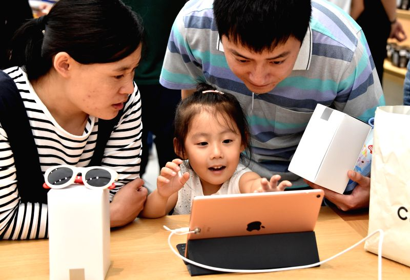 JINAN, May 21, 2016 - People experience Apple products in an Apple retail store in Jinan, east China's Shandong Province, May 21, 2016. The first Apple retail store in Jinan opened on Saturday.