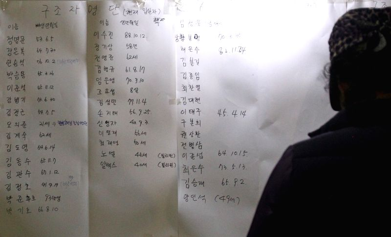 A relative of missing people checks name list in Jindo, South Korea,  April 16, 2014. A passenger ship with 462 people aboard, mostly high school students, sank in ..