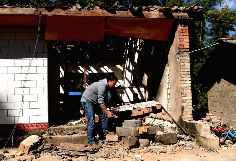 Zhou Xinwei of the Dai ethnic group searches for useful articles on the debris of a collapsed house at quake-hit Qianying Village of Yongping Town in Jinggu Dai and Yi Autonomous County, ...