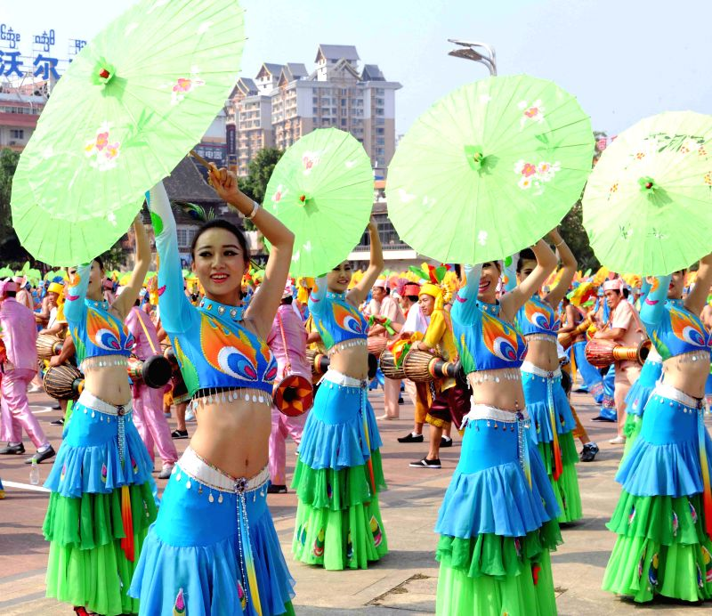 Girls of Dai ethnic group perform umbrella dance during a cultural demonstration to celebrate the New Year of Dai ethnic group in Jinghong City, Dai Autonomous ...