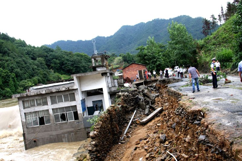 A road is destroyed by flood water in Xiushui County of Jiujiang City, east China's Jiangxi Province, July 4, 2014. Heavy rainfall hit parts of Jiangxi in last two .