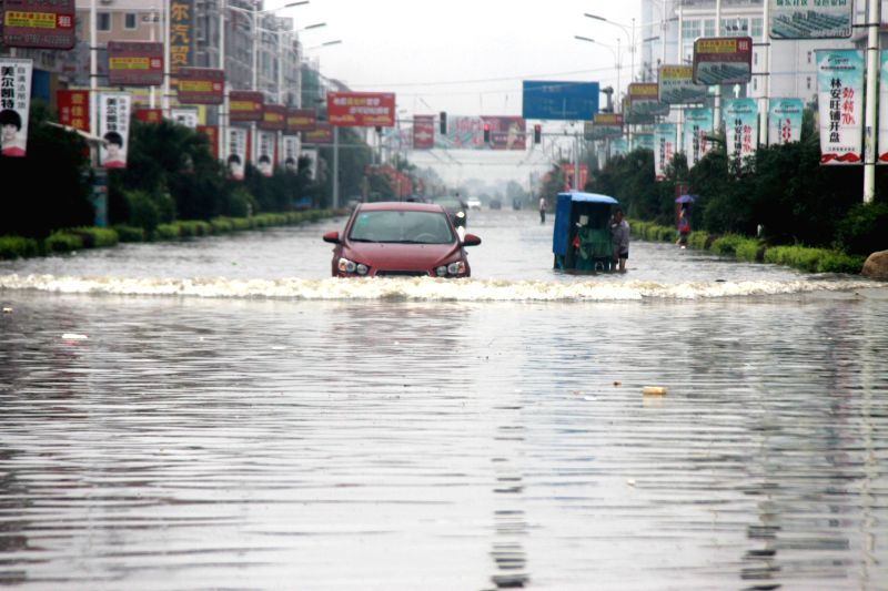 A vehicle runs on flooded road in Ruichang City, east China's Jiangxi Province, July 5, 2014. Heavy rainfall hit parts of Jiangxi in last two days. (Xinhua/Wei ...