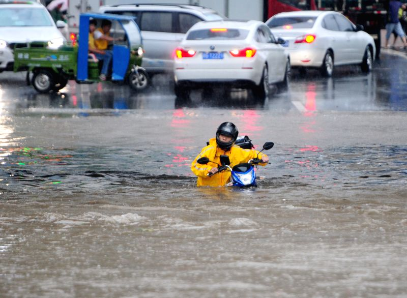 JIUJIANG, June 1, 2016 - A man pushes his motorbike on a flooded street in Jiujiang, east China's Jiangxi Province, June 1, 2016. Torrential rain hit the city and caused flood.