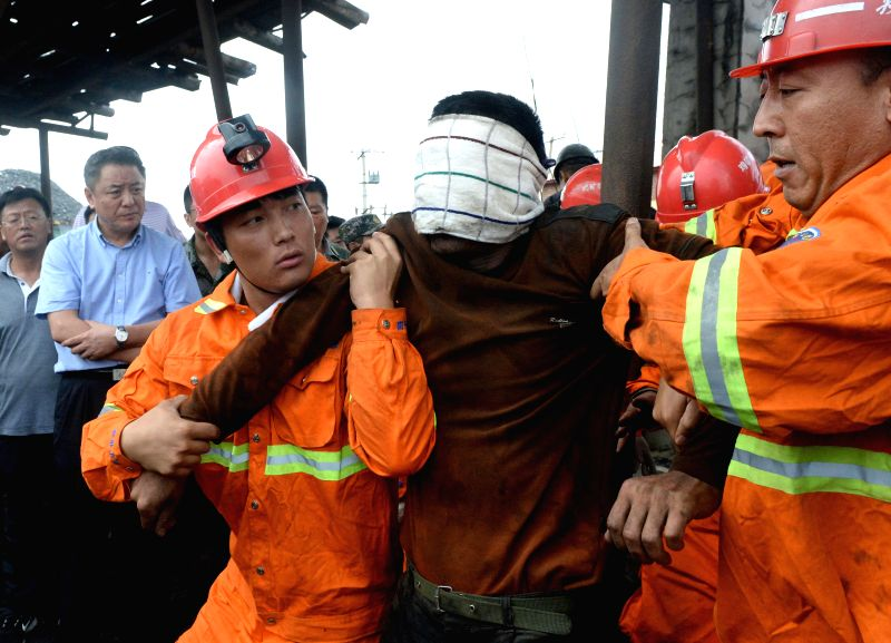 A miner (C) is rescued from a flooded coal mine of privately-owned Anzhishun Coal Mine in Jixi, northeast China's Heilongjiang Province, Aug. 15, 2014. Nine people ...