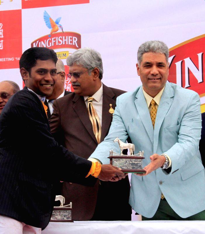 Jockey Suraj Narredu receives the winning trophy from Samar Singh Sheikhawat during Kingfisher Derby 2014 at Bangalore Turf Club in Bangalore on July 13, 2014. - Samar Singh Sheikhawat