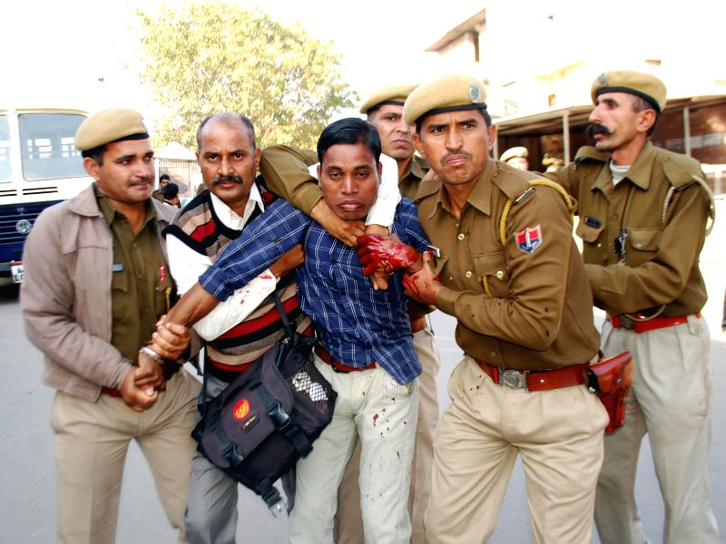Police take away the man who stabbed Rahul Sachan, a witness in Asaram rape case in Jodhpur court premises on Feb 13, 2015.