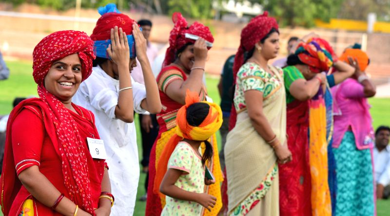 Women participate in a turban tying contest organised on Jodhpur Sthapana Divas at Umaid Stadium in Jodhpur on May 12, 2015.