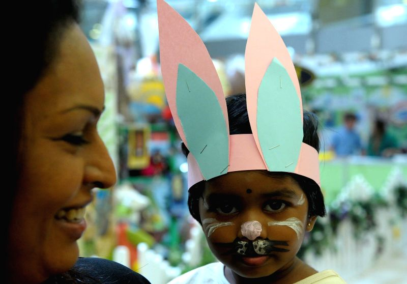 A woman shops with her child dressing up as Easter rabbit at an Easter market at Sandton City in Johannesburg, South Africa, on April 18, 2014. (Xinhua/Li ...