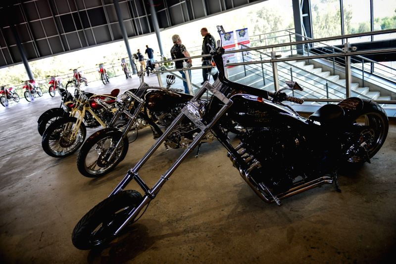 JOHANNESBURG, May 26, 2017 - Exhibitors chat with each other beside the customized motorcycles on the opening day of the second South Africa Bike Festival at Kyalami, north of Johannesburg on May 26, ...
