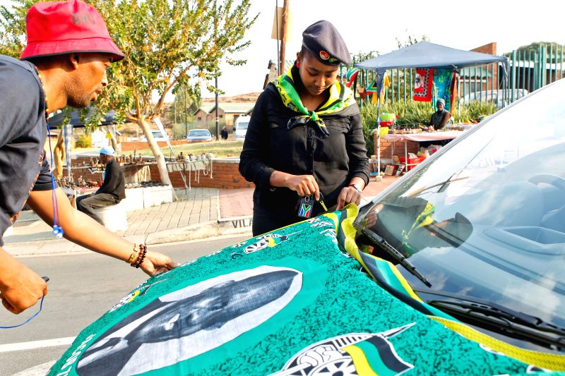 Supporters of African National Congress (ANC) tie up a flag on their car in Soweto, Johannesburg, South Africa, May 6, 2014. According to South Africa's ...