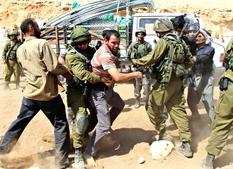 Israeli soldier attacks a Palestinian Bedouin who tries to reach the remains of his tent after it was demolished in Khirbet Makhoul village in the Jordan ...