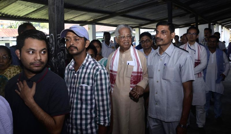 Jorhat: Former Assam Chief Minister Tarun Gogoi and son, Congress' Lok Sabha candidate from Kaliabor, Gaurav Gogoi stand in queue to cast vote for Lok Sabha election at a polling station, in Assam's Jorhat, on April 11, 2019. (Photo: IANS)
