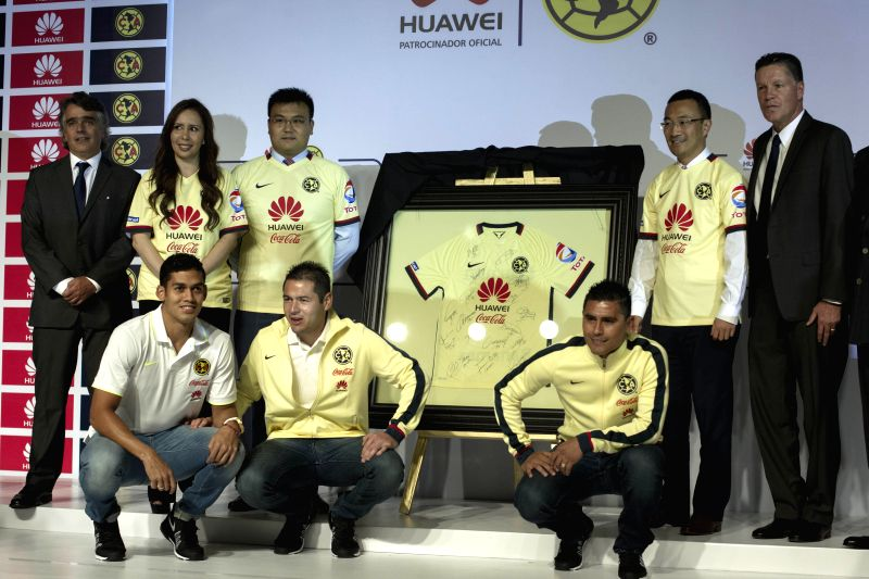Jose Romano (L), President of America Football Club, and Ricardo Pelaez (R), Sporting President pose next to players and directives of the Chinese ...