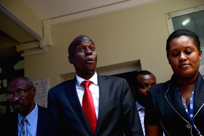 Jovenel Moise (C), candidate to Haiti's Presidency for the ruling Haitian Party Tet Kale (PHTK), reacts as he leaves the Provisional Electoral Council (CEP, ...