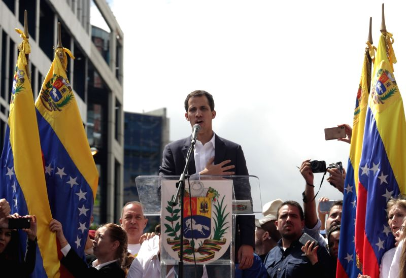 "Juan Guaido (C), head of the opposition-controlled National Assembly, delivers a speech at the Francisco de Miranda avenue, in Caracas, Venezuela, on Jan. 23, 2019. Venezuelan President Nicolas Maduro on Wednesday announced he was severing ""diplomati(Image Source: IANS News)"