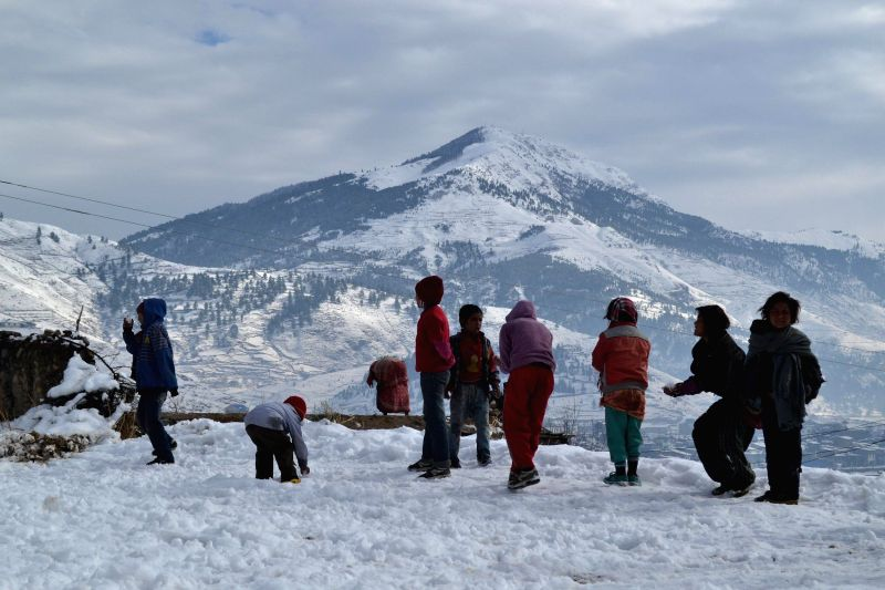 Local children play with snow in Jumla, Nepal, Dec. 14, 2014. The falling temperature brought snowfall  to the mountainous districts of Nepal.