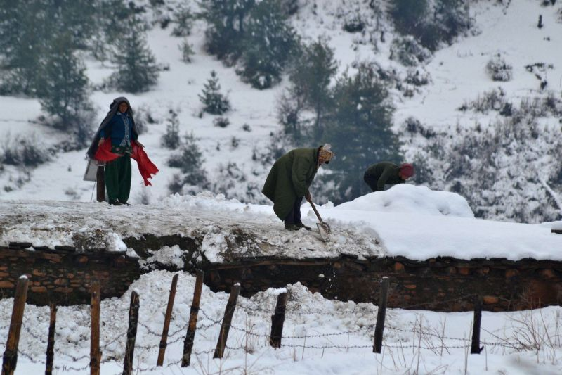 Local people clean their roofs covered with snow after the heavy snowfall in Jumla, Nepal, Dec. 14, 2014. Most of the mountainous districts including Jumla were hid hard due to snowfall after .