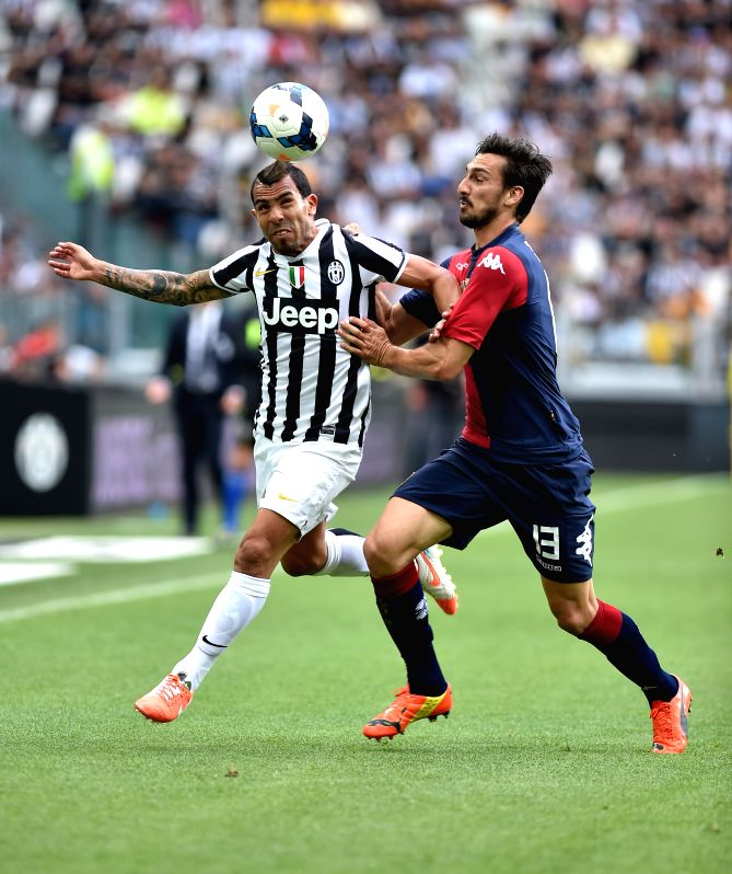Juventus' Carlos Tevez (L) vies with Cagliari's Davide Astori during the Italian Serie A soccer match in Turin, Italy, May 18, 2014. Champions Juventus became the ..