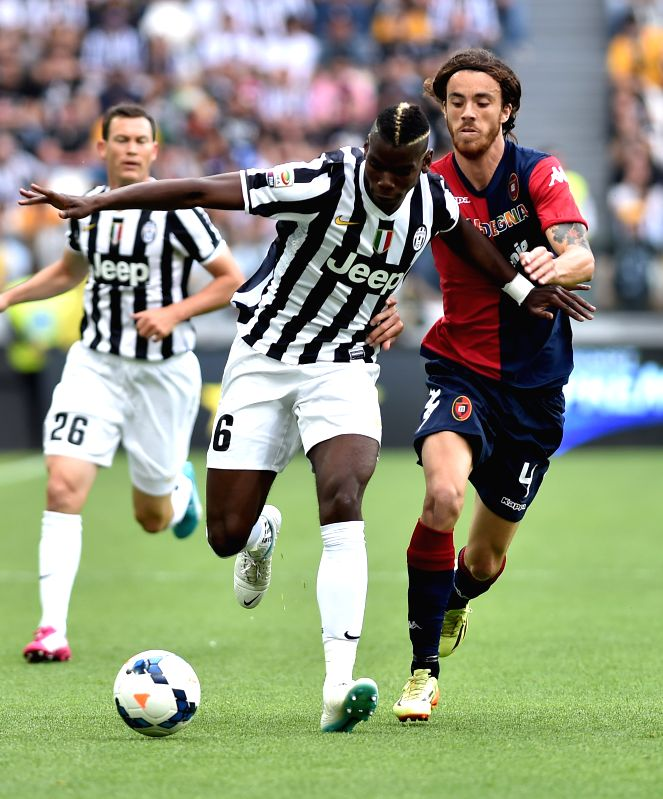 Juventus' Paul Pogba (C) vies with Cagliari's Andrea Tabanelli (R) during the Italian Serie A soccer match in Turin, Italy, May 18, 2014. Champions Juventus became .