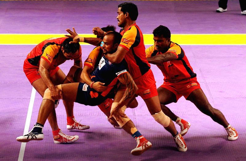 Kabbadi players of Bengaluru Bulls and Bengal Warriors in action during a Pro Kabaddi League match at Netaji Indoor Stadium in Kolkata on July 30, 2014. Bengaluru Bulls  won the match. (Score - 46 - .